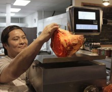 Eddy Shin, owner of A Cut Above Butchers, weighs a piece of grass-fed beef. (Michael Ryan michael@smdp.com)