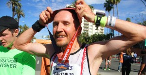 Phil McNally, from Eagle Rock, Calif., places his medal around his neck after fiinishing the 2014 Los Angeles Marathon on Sunday. (Daniel Archuleta daniela@smdp.com)