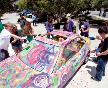 Students from Santa Monica Alternative School House (SMASH) paint the 'SuperSMASH' car in 2011. (File photo)